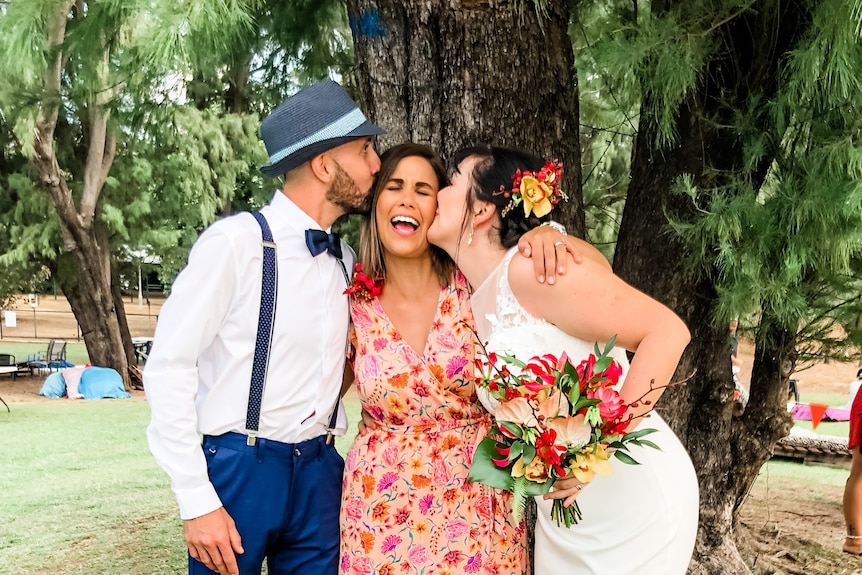 A just-married bride and groom each kiss the celebrant on a cheek at an outdoor ceremony