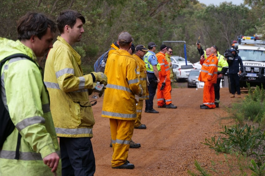 A row of men wearing high-vis clothing stand in a row next to bushland.