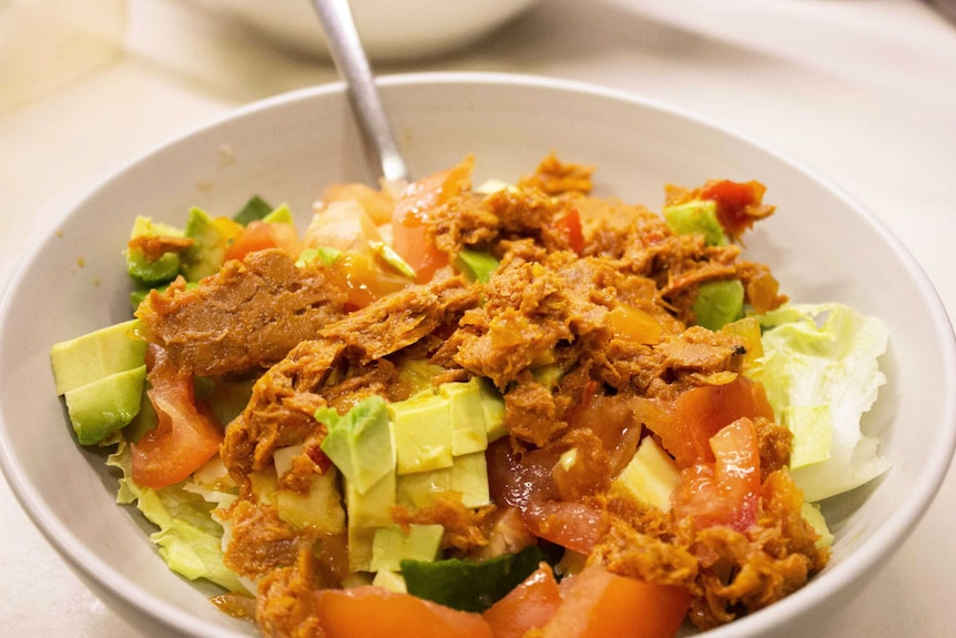 Tuna on salad in a bowl, a meal that's easy to fit into your meal preparation schedule and a good use of leftovers.