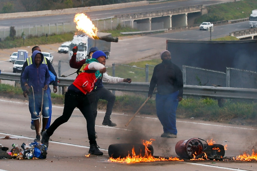 Supporters of former South African presidentJacobZumablock a freeway with burning tyres