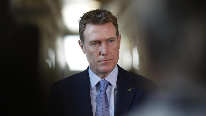 A man with brown hair wearing a suit and tie looks to the right, he is in focus with people closer to the camera out of focus
