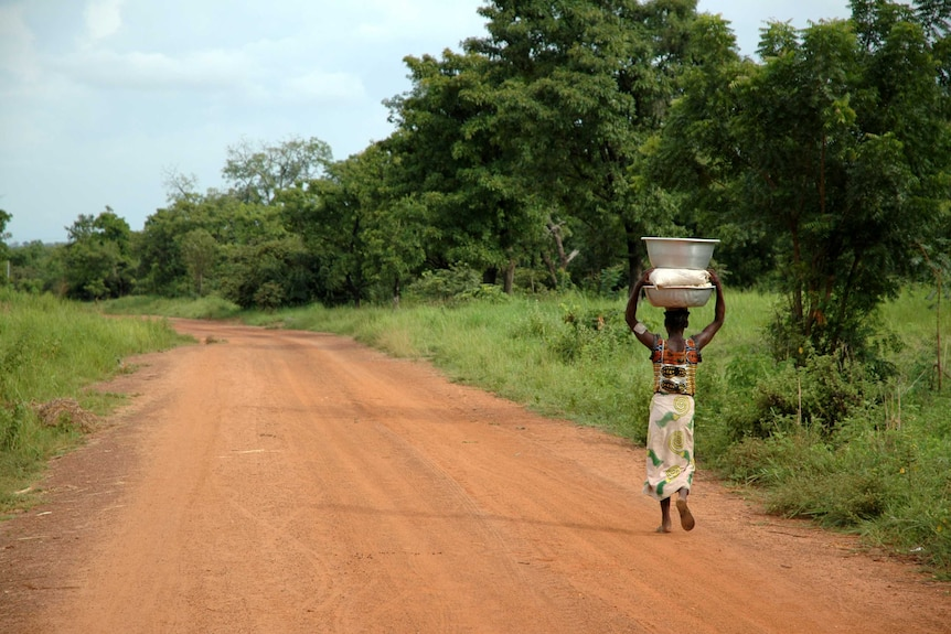 A woman carries water on her head along a dirt road, with grass and large trees in the background.