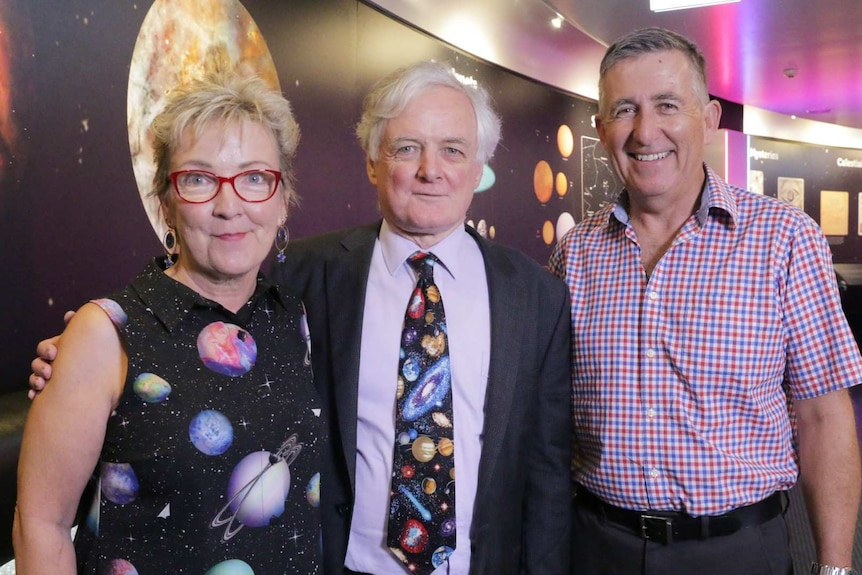 Three people smile wearing space themed clothing.