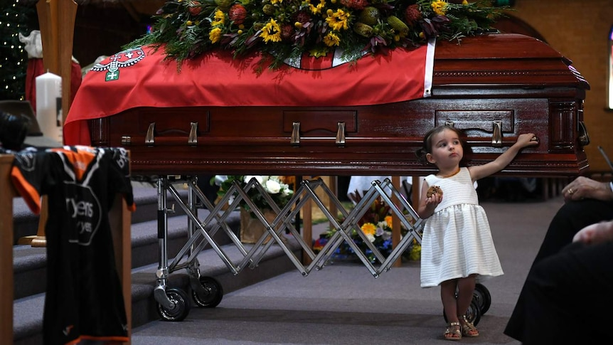 A young girl touches a large wooden casket
