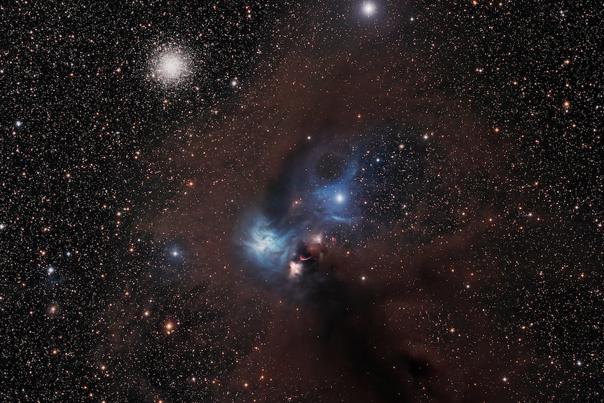 Black sky with twinkling stars and two blue hues in the centre
