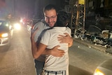 Two men hug each other on the streets of Gaza.