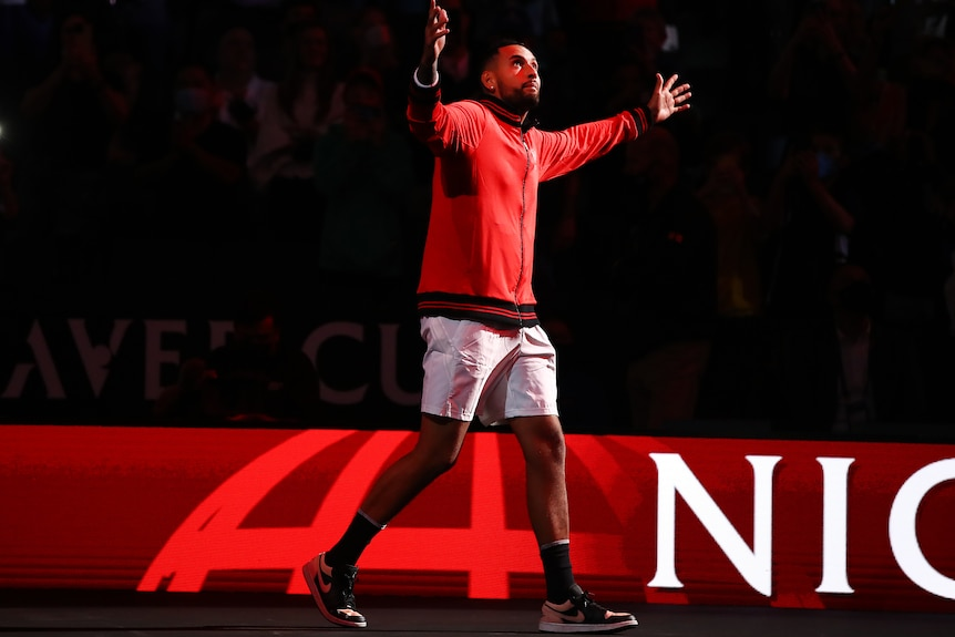 Nick Kyrgios raises his arms to the crowd as a red light welcomes him to the court