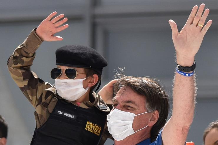 Brazil's President Jair Bolsonaro, wearing a mask against the spread of coronavirus, carries a child.