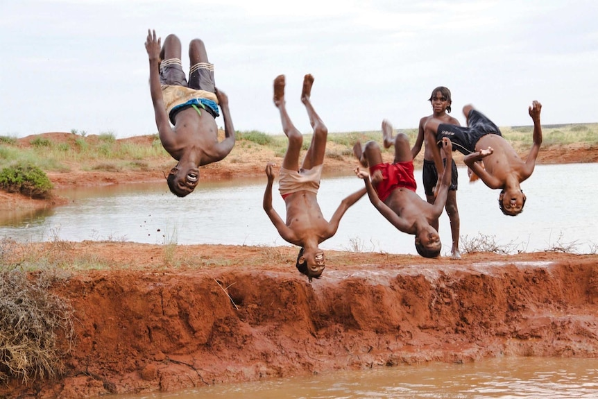 Four boys doing a backflip after swimming