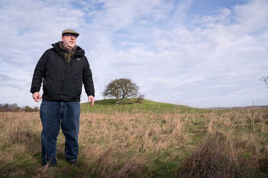 Brian Edwards in front of a Stonehenge burial mound.