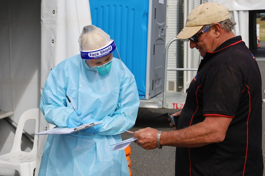 A woman nurse in full PPE filling out paperwork on a clipboard, looking at a card that a man is holding out to her