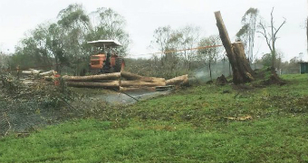 A tractor and a tree that upturned itself and crushed a 12 year old boy after falling in a severe storm in the South Burnett.