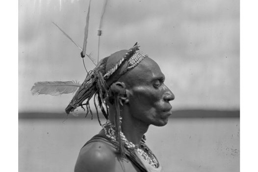 Black and white medium shot of a man standing sideways wearing traditional dress.