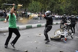 Protester attacks riot police in Tehran after Iran election.