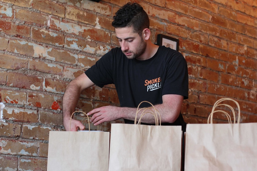 Tom Jacobson packing brown paper bags with meals for delivery