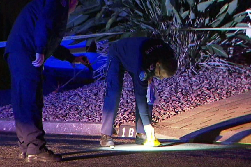 Two police officers place a marker on the ground at the crime scene
