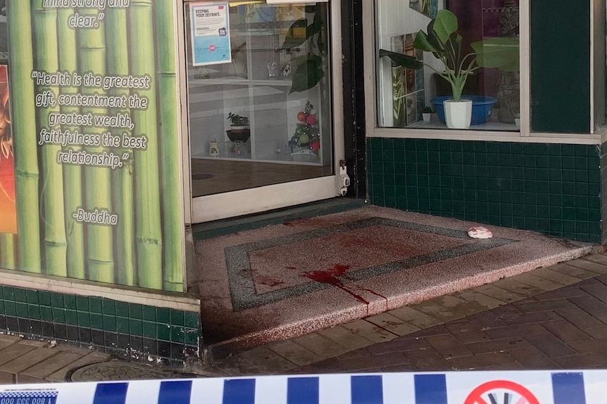 A cafe facade cordoned off with police tape. Blood is pooling at the door.