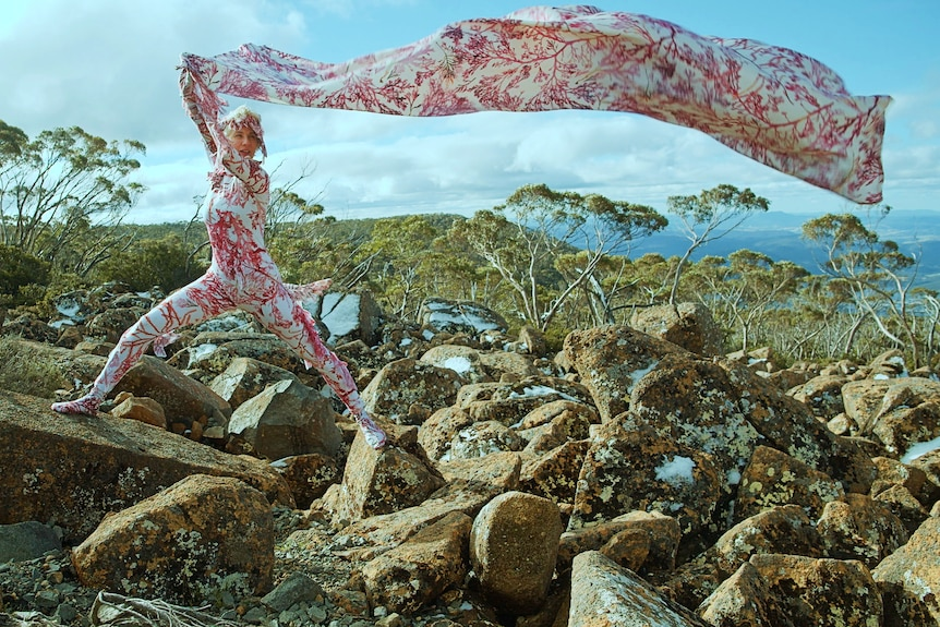 A woman in a red and white body suit stands on rocks holding a matching length of fabric blowing in the wind.