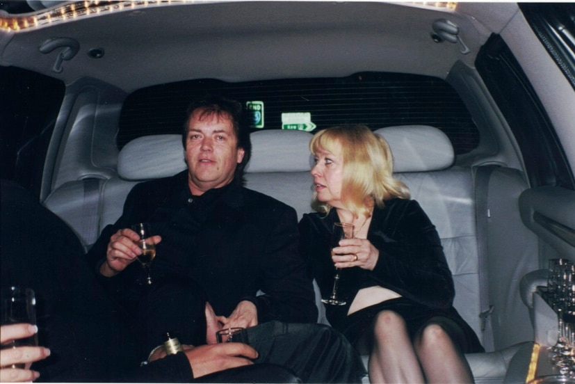 Terence and Christine Hodson in the back of a limo, each have a glass of champagne.