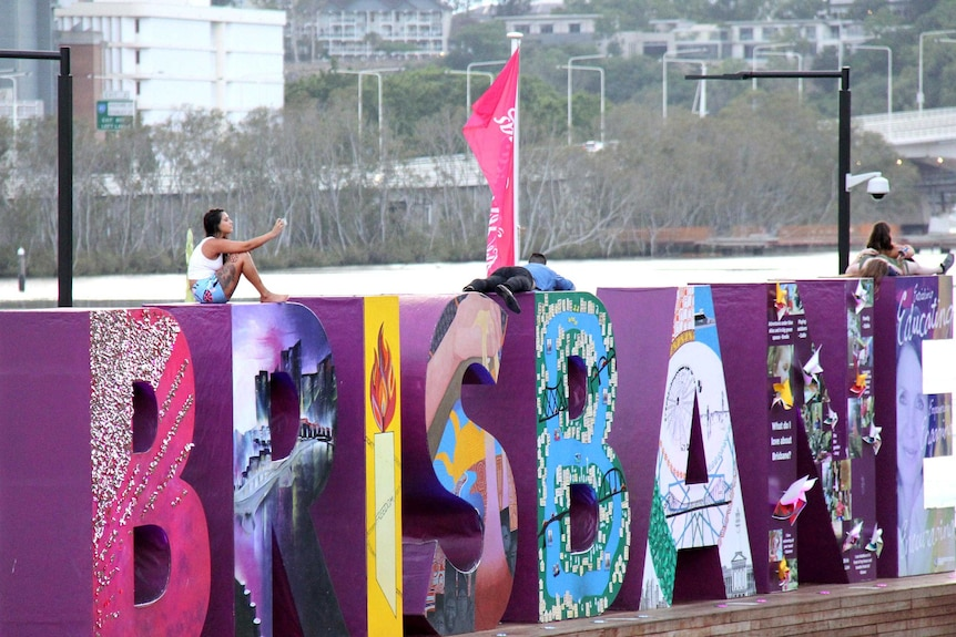 Revellers sit on the Brisbane sign at South Bank, Brisbane, in the early hours of New Year's Day, January 1, 2015.