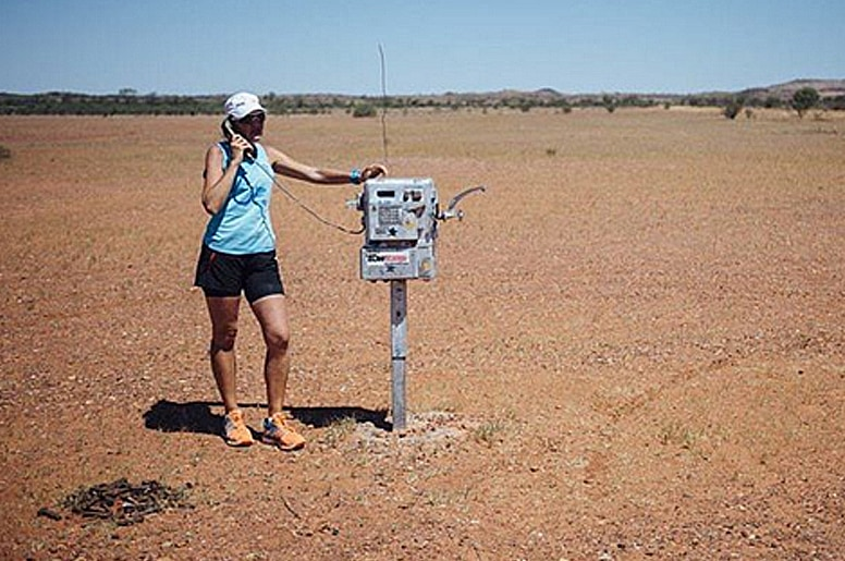 Mina Guli stands at an old telephone, during a stop in the Simpson Desert, South Australia.