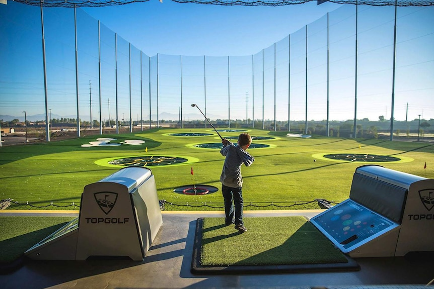 Child swings a golf club playing at a range at Topgolf Gold Coast, date unknown.