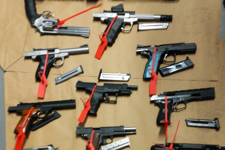 More than a dozen handguns lie on a table with red tags on them.