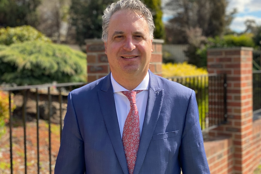 A photo of Paul Guerra wearing a blue suit and red textured tie.