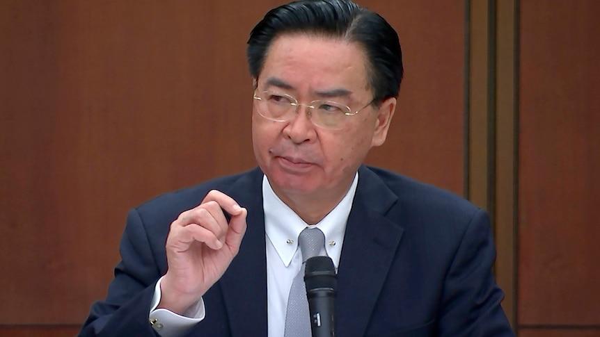身着西装的台湾男子拿着话筒打了个手势。
