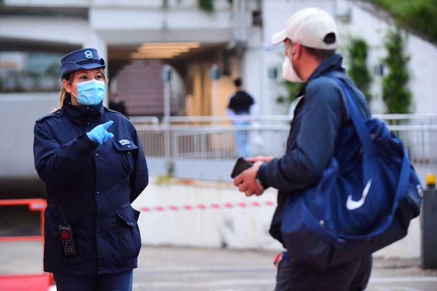 A police officer in a face mask and gloves pointing at a man