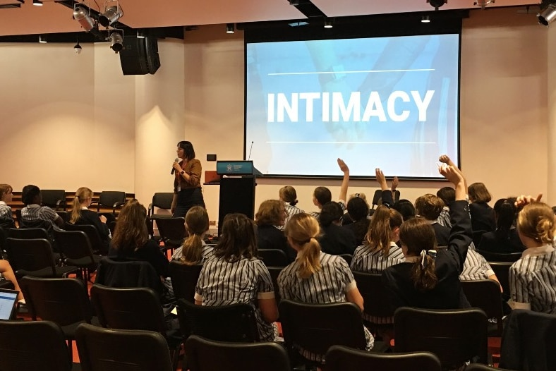 A woman holds a microphone in front of an image saying intimacy and a group of school children in chairs.