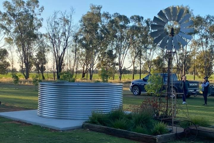 A steel tank filled with water sits on concrete slab next to windmill.