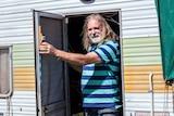 Roland Gopel stands in the doorway of his caravan.