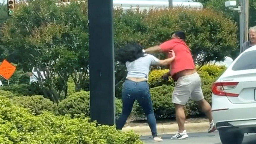 A man and a woman brawl in the carpark of a petrol station.