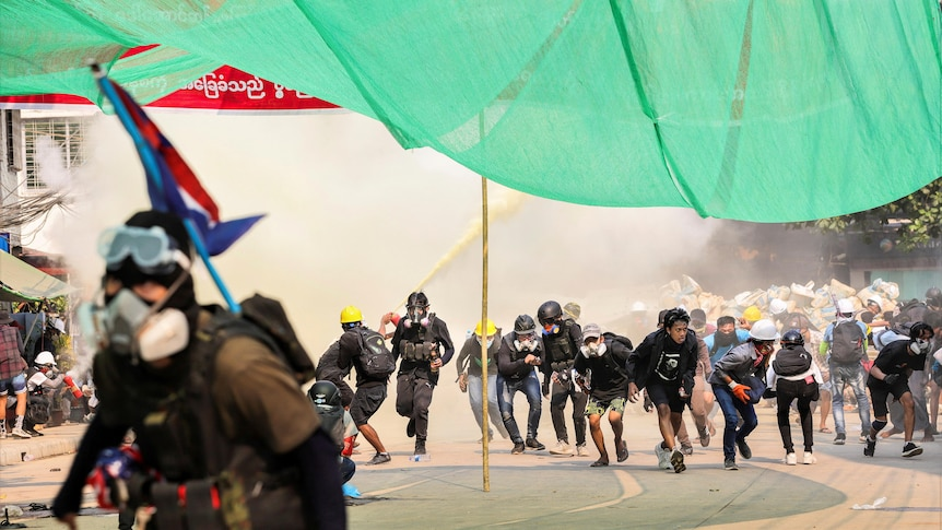 A group of street protesters duck under a green canopy with smoke behind them.