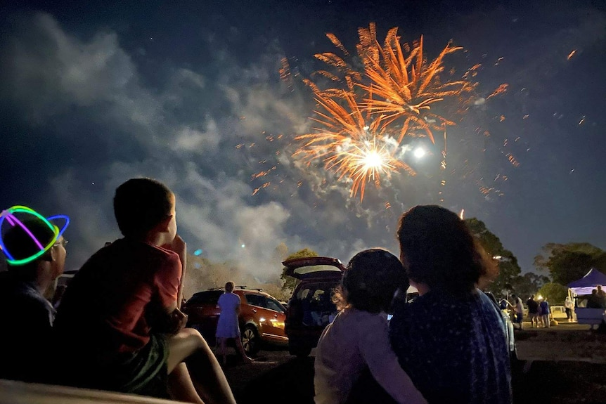 Families watch the fireworks from a drive-in theatre at Ipswich.