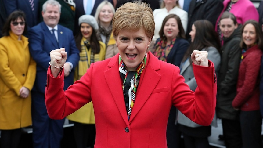 Scottish First Minister Nicola Sturgeon in a red blazer cheering.