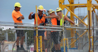 A group of construction workers stand on a building site.