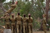 Boy leans backward for trust exercise where eight soldiers in training are preparing to catch him