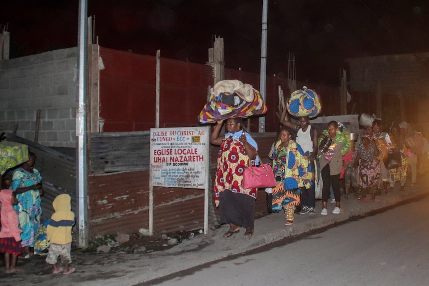 A long line of people flee with their belongings  bundled up on their heads in the night.