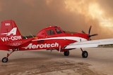 plane stationary on ground with smoke in the background