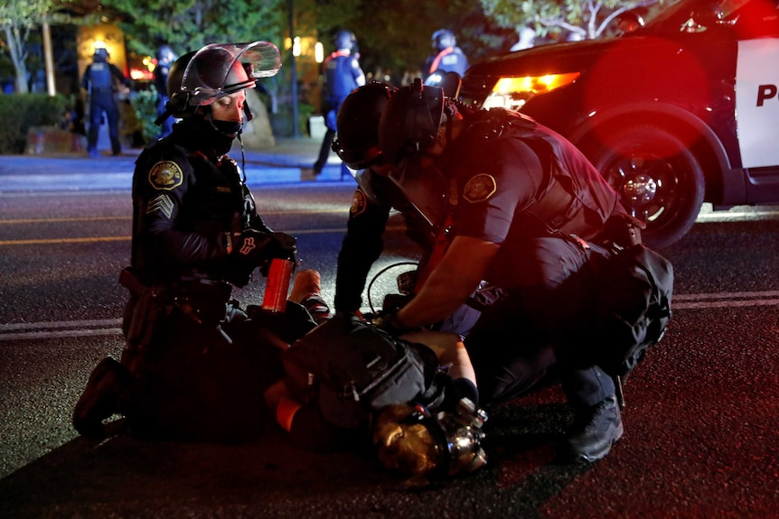 Police officers detain a demonstrator during a protest against police violence and racial injustice in Portland.