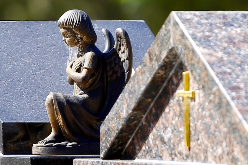 A small statuette of a weeping angel sits atop an unidentified gravestone in a cemetery.