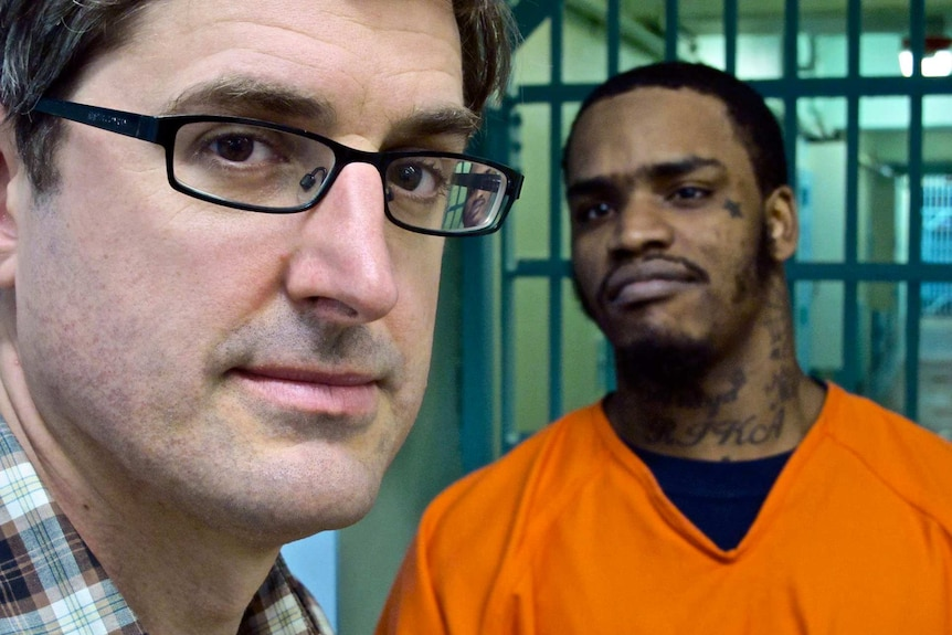 Louis Theroux standing with a prisoner in an orange prison suit