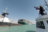 The giant Ever Given ship is accompanied by Suez Canal tugboats as it moves in the Suez Canal.