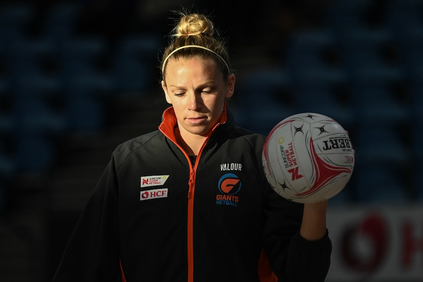 Jo Harten looks down and holds the ball in her left hand as sun floods half of her face in a dark stadium