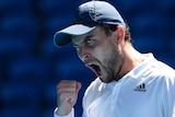 Aslan Karatsev pumps his fist and shouts at the Australian Open.