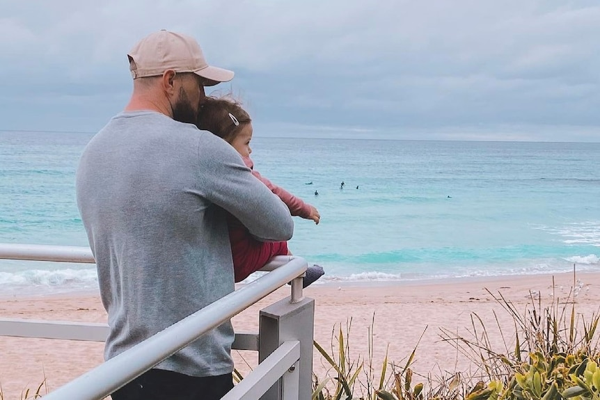 Jordan Rankin holds his baby daughter and looks out at the surf from a viewing platform.