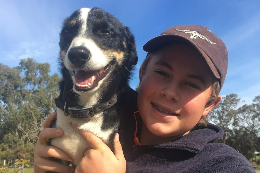 A teenager in a baseball cap and navy jumper holds up a dog.
