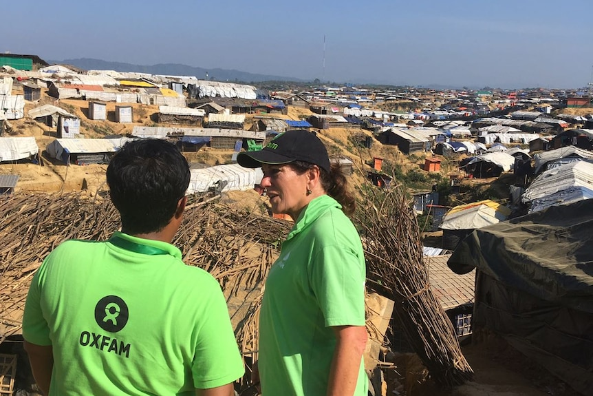 Two aid workers overlook a camp